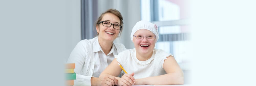 Portrait of happy mother and girl with Down Syndrome at home