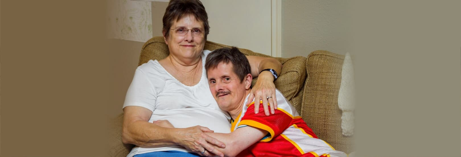 men with Downs Syndrome, hugs his sister as they sit on a couch